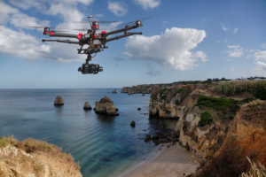 A drone with raised landing gears and a camera flying in beautiful cloudy skies along spectacular sea cliffs with a calm ocean in the background